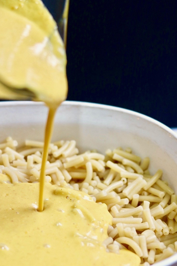 cheese sauce being poured on macaroni noodles
