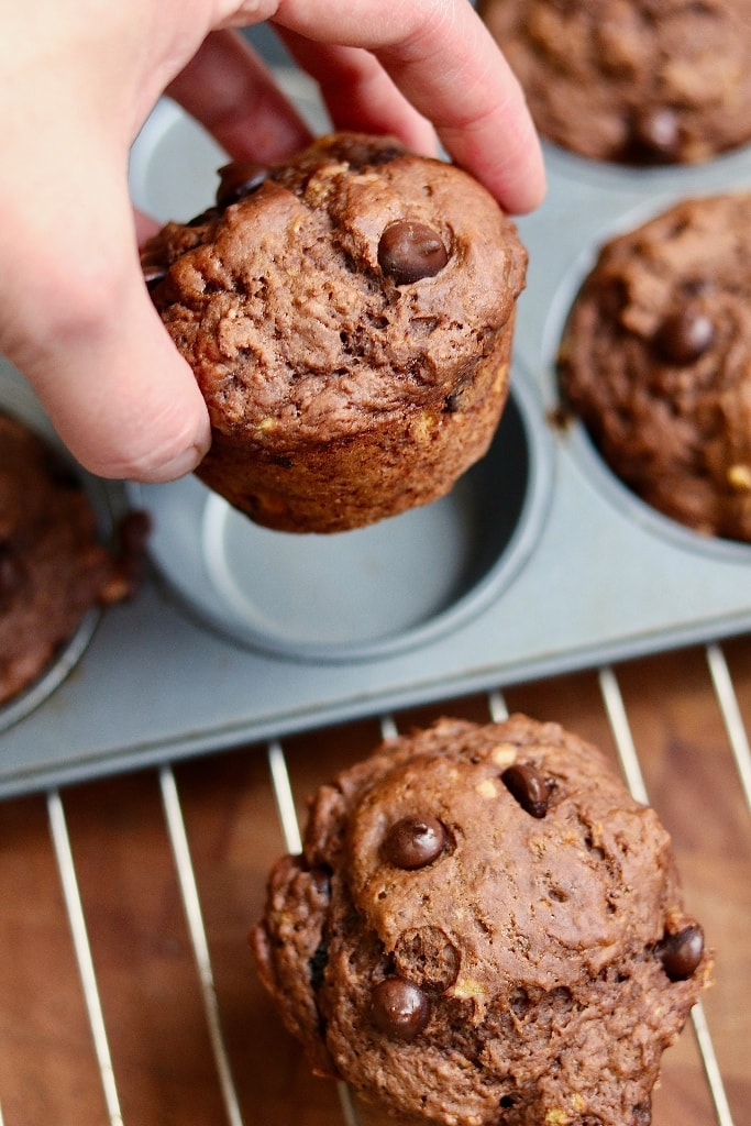 chocolate banana muffin being taken out of muffin tin