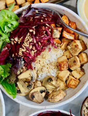 vegan buddha bowl full of veggies rice tofu and peanut dressing