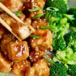 vegan orange chicken in a bowl with broccoli and chopsticks