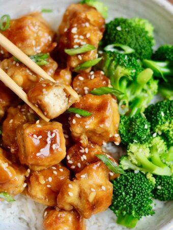 vegan orange chicken in a bowl with broccoli and chopsticks