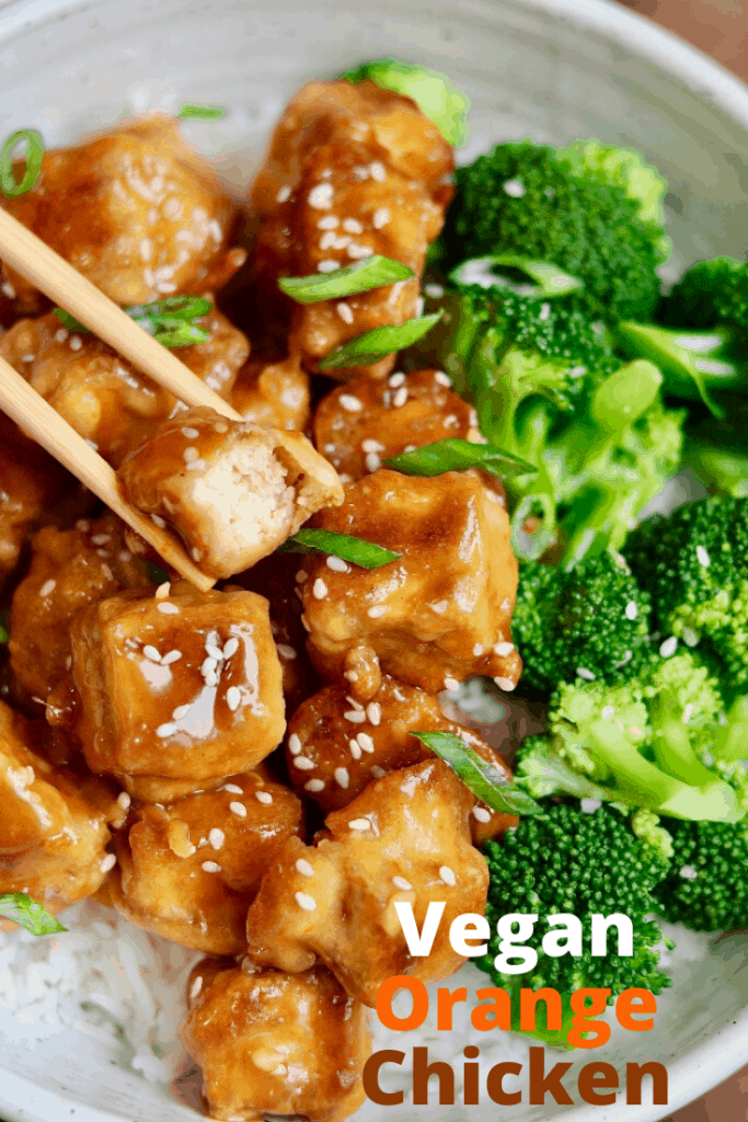 Vegan Orange Chicken in a white bowl with rice broccoli and chopsticks