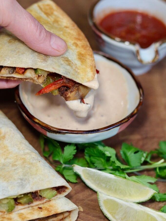 vegan quesadilla being dipped in sauce