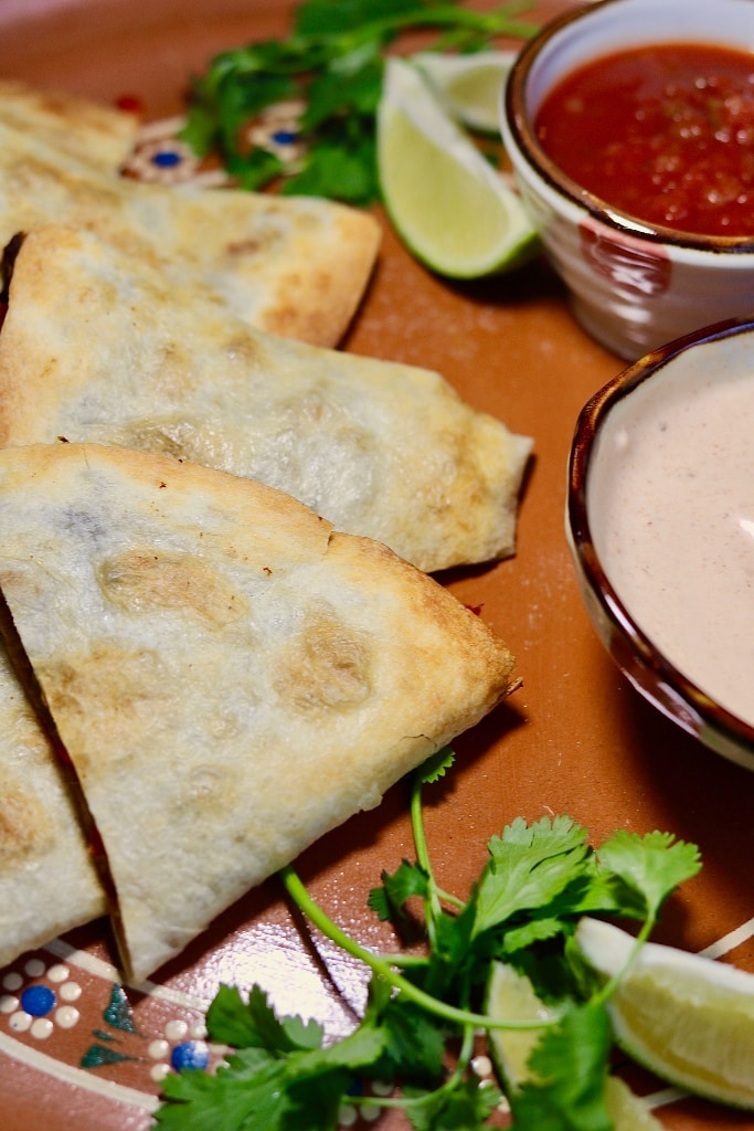 vegan quesadillas on a tray with sauce and salsa