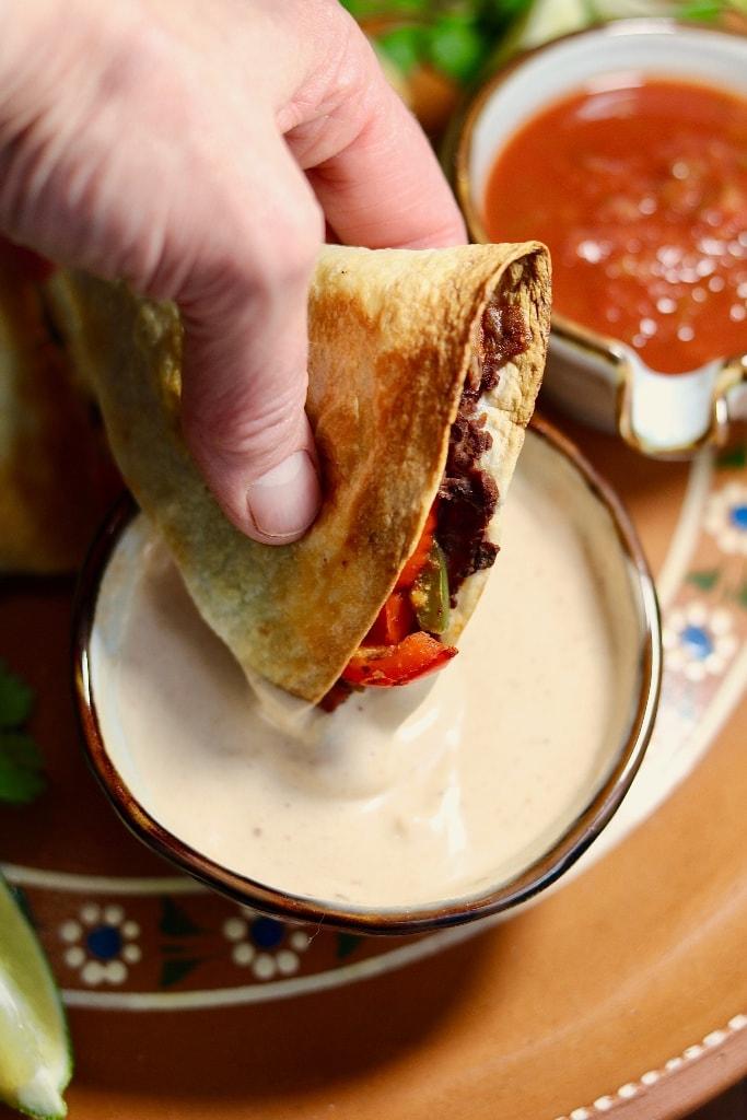 vegan quesadilla wedge being dipped in sauce