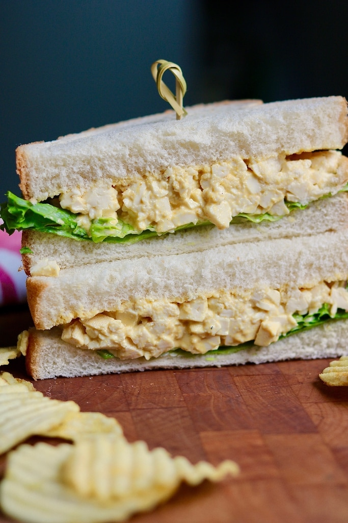 vegan egg salad sandwich stacked on a cutting board with potato chips