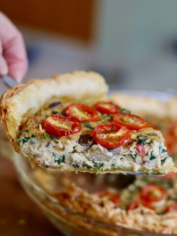 slice of vegan quiche being held in air with a pie server