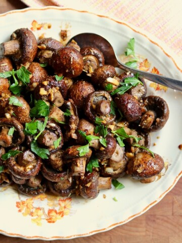 roasted mushrooms on a plate with a serving spoon