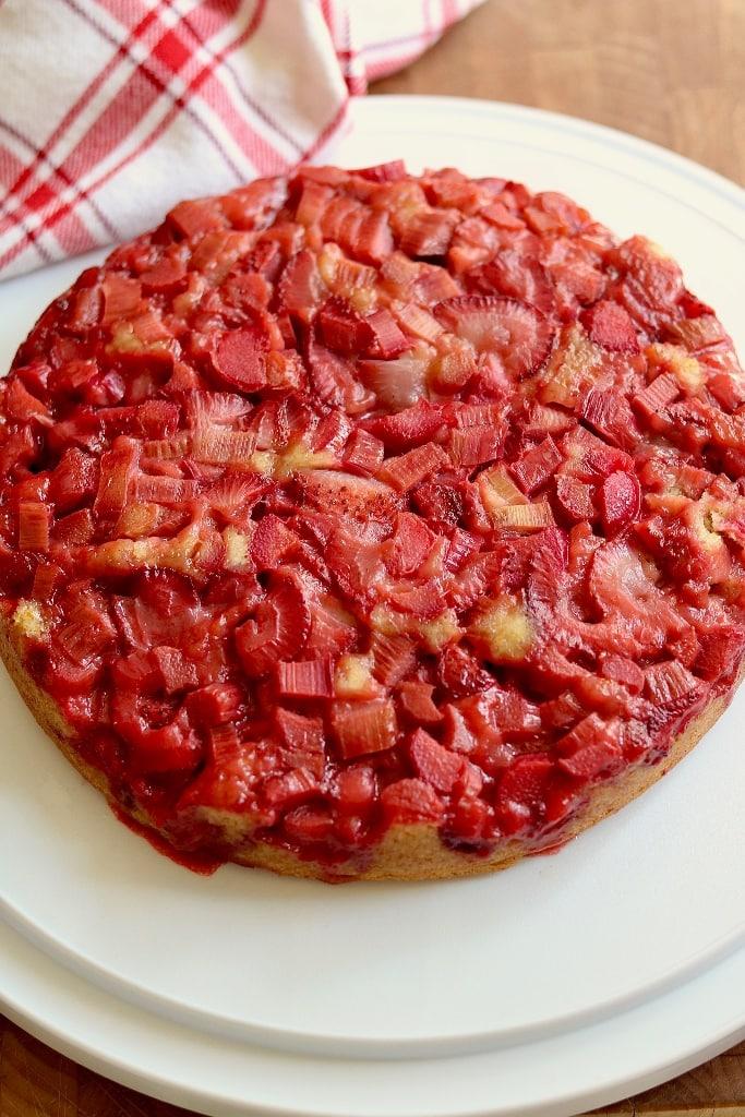 strawberry rhubarb cake on a cake platter