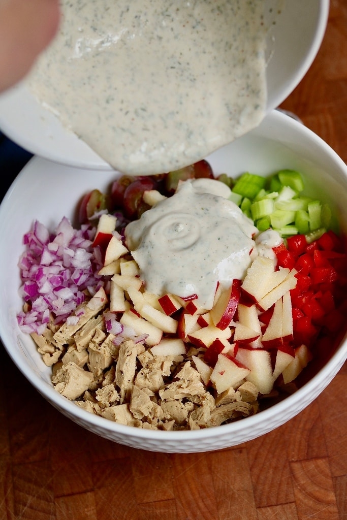 dressing being poured on vegan chicken salad