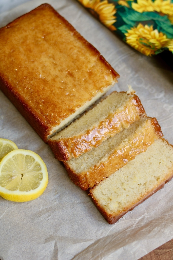 top view of lemon loaf partially sliced on parchment paper