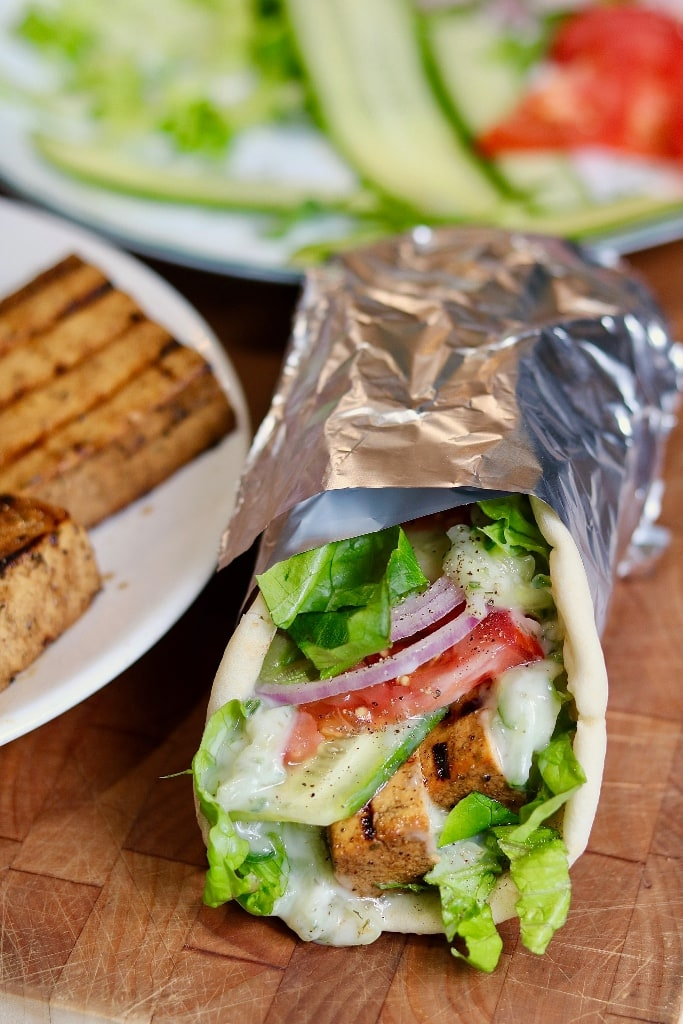 vegan gyro wrapped in foil on a wooden cutting board beside a plate of grilled tofu and veggies