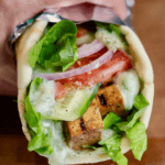 vegan gyro wrapped in foil being held