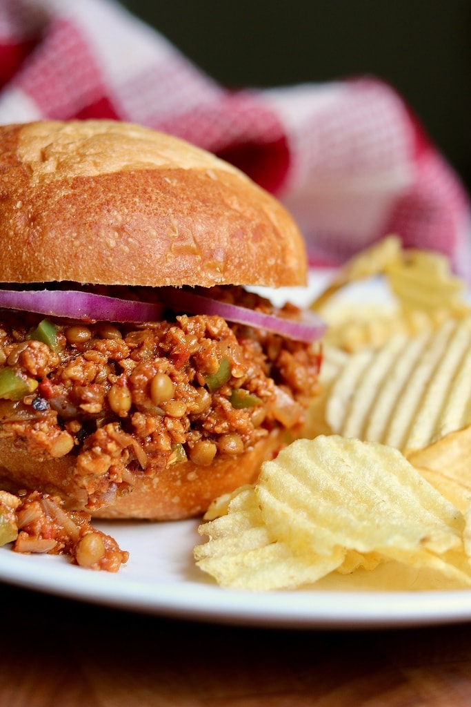 close up of a vegan sloppy joes with a side of potato chips