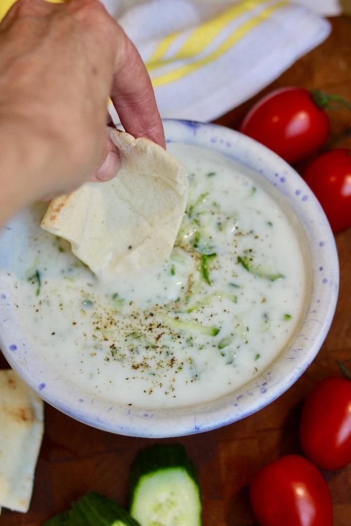 pita being dipped in a bowl of vegan tzatziki sauce