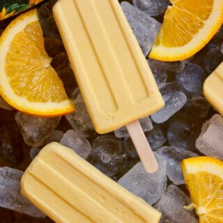 two creamsicles on a bed of ice with orange slices