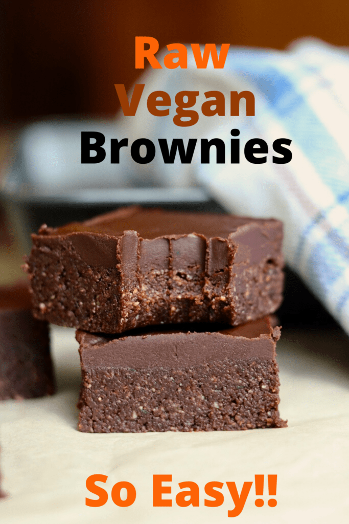 two vegan brownies stacked on parchment paper