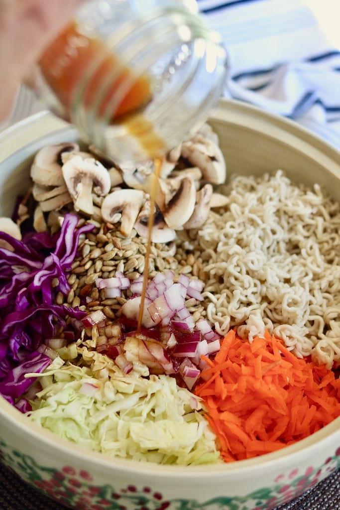 dressing being poured over ramen salad