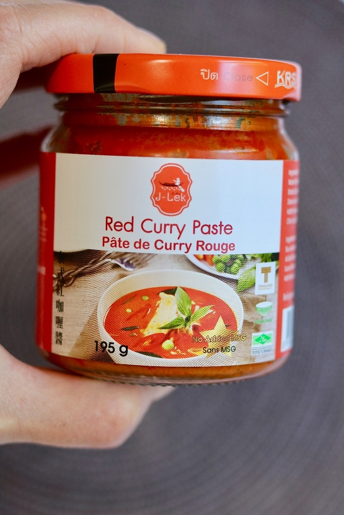 a jar of red curry paste being held