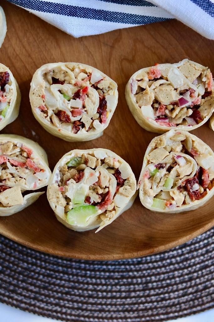 pinwheel tortilla roll ups on a wooden serving platter