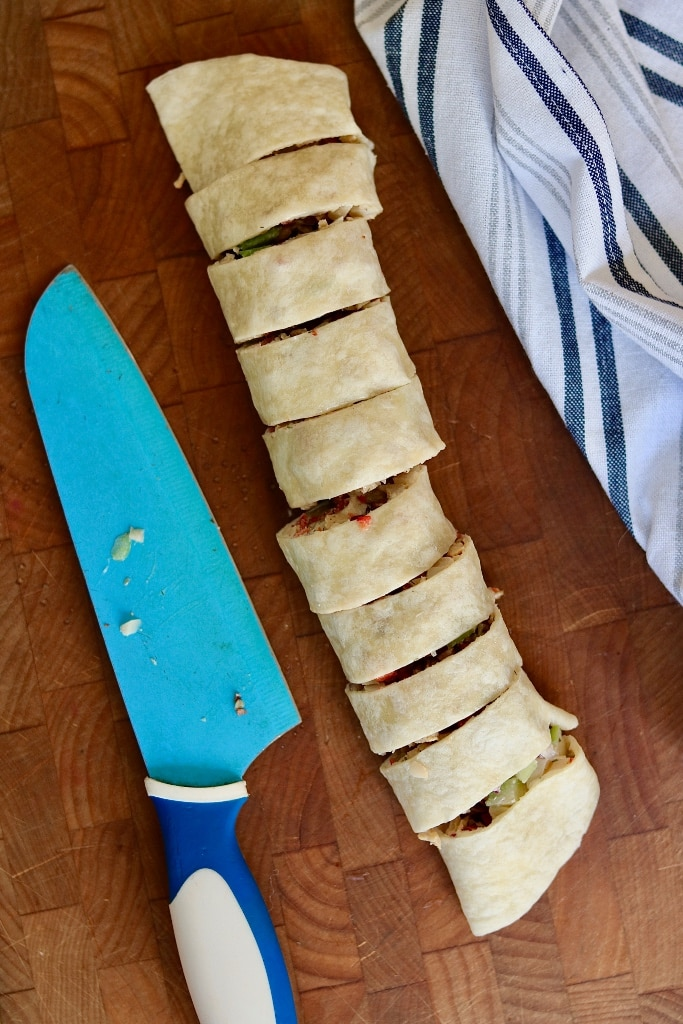 tortilla roll sliced into pinwheels on a cutting board