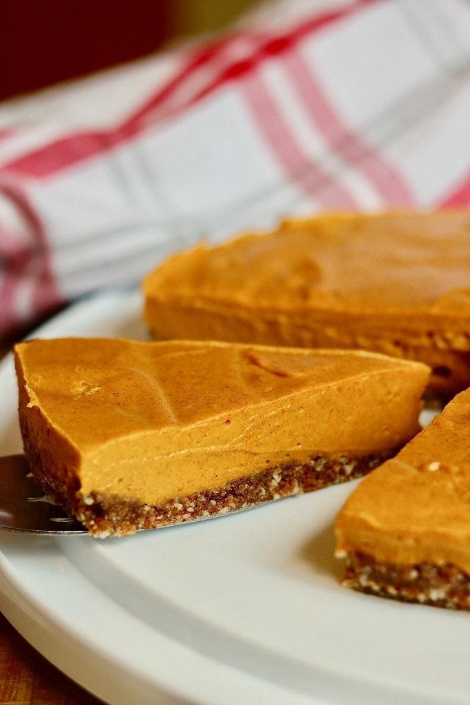 A slice of vegan pumpkin cheesecake on a pie server