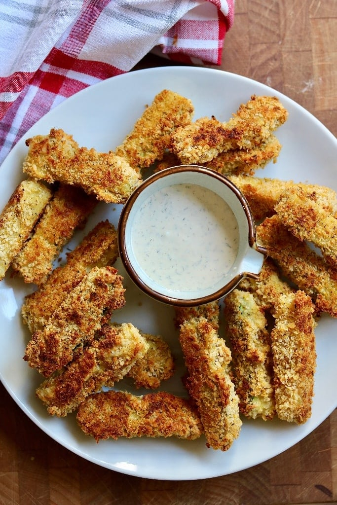 vegan zucchini fries on a white plate with ranch dressing