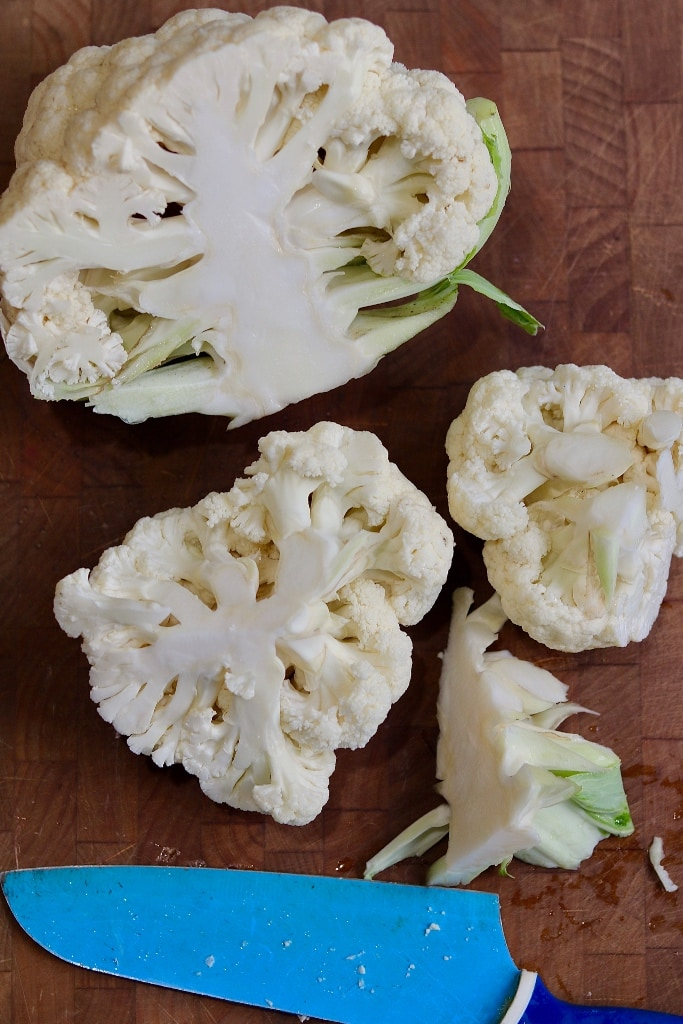 head of cauliflower being cored and chopped on cutting board