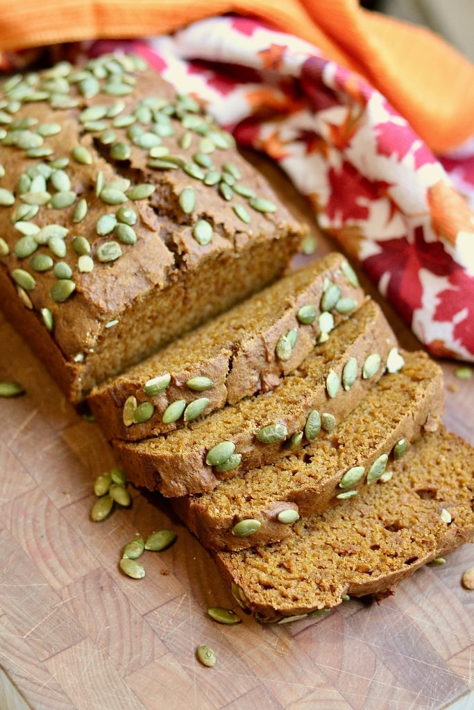 a loaf of pumpkin bread partially sliced on a cutting board