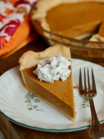 a slice of vegan pumpkin pie on a white plate