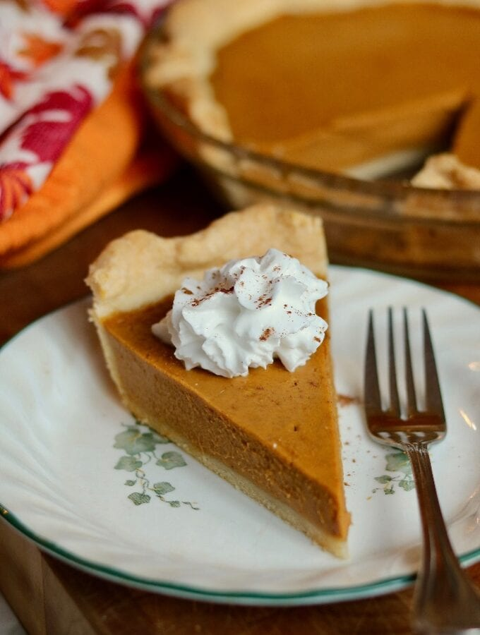 a slice of vegan pumpkin pie on a white plate