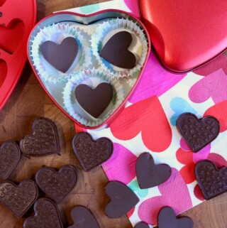 dairy free chocolates unmolded on table beside chocolate heart valentine tin