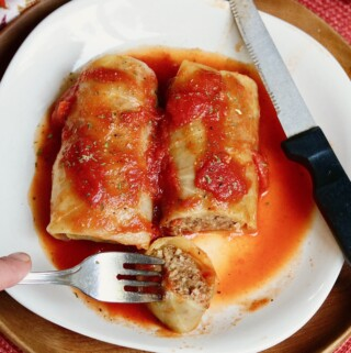 two vegan cabbage rolls on a white plate with fork and knife