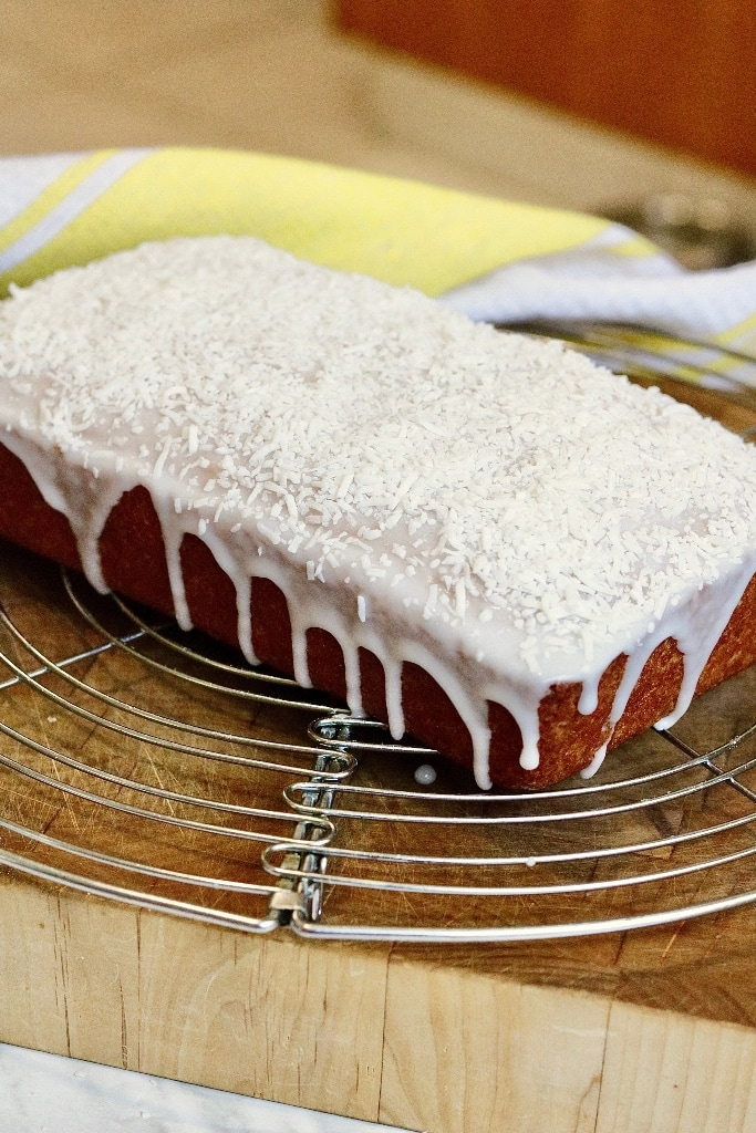 a loaf of coconut bread on cooling rack with frosting