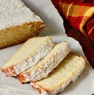 coconut loaf cake sliced on cutting board