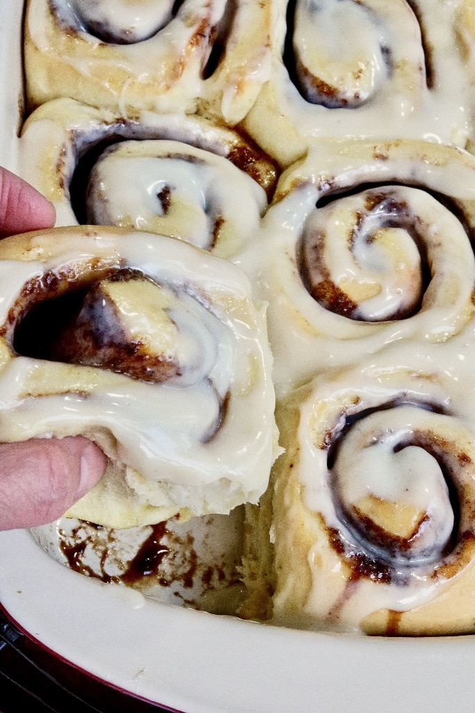 cinnamon roll being taken out of dish
