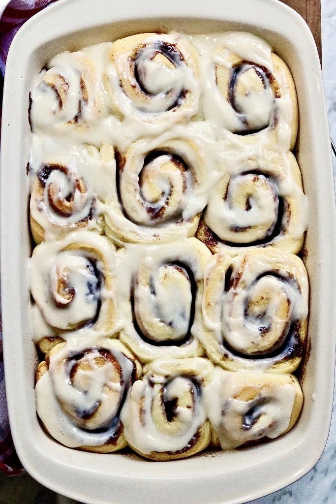 a pan of freshly baked and frosted vegan cinnamon rolls