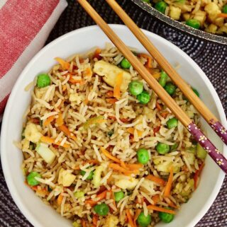 vegan fried rice in a bowl with chopsticks