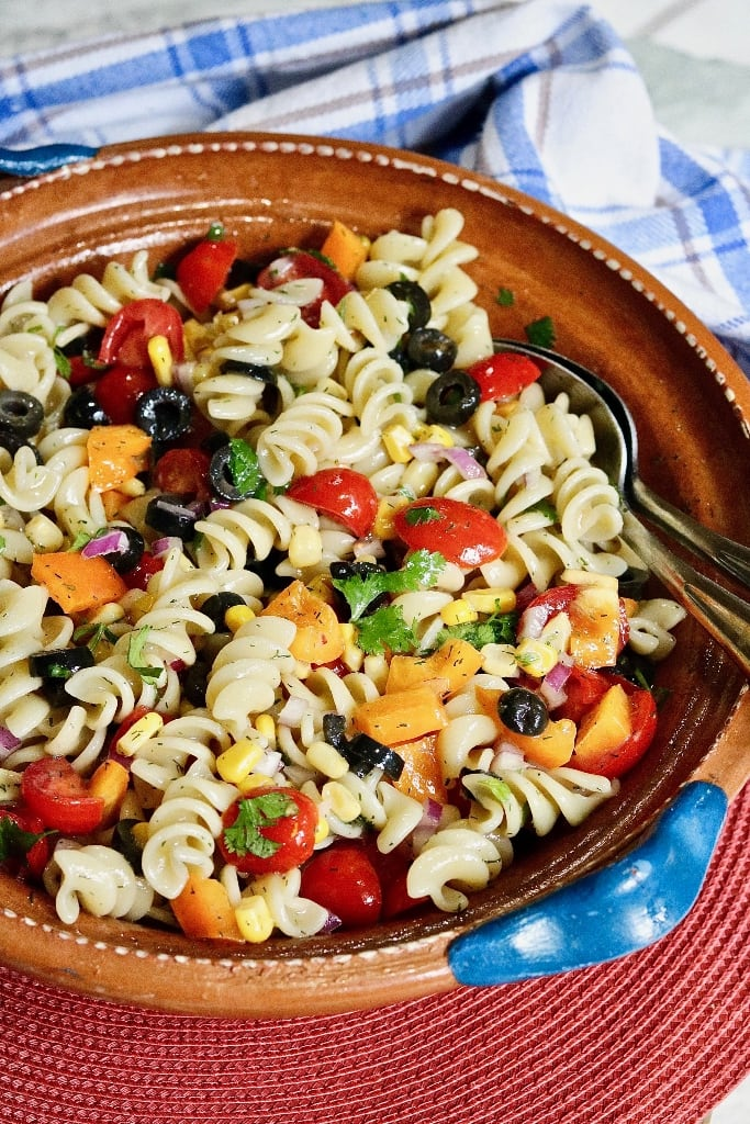 pasta salad in a bowl with serving spoons
