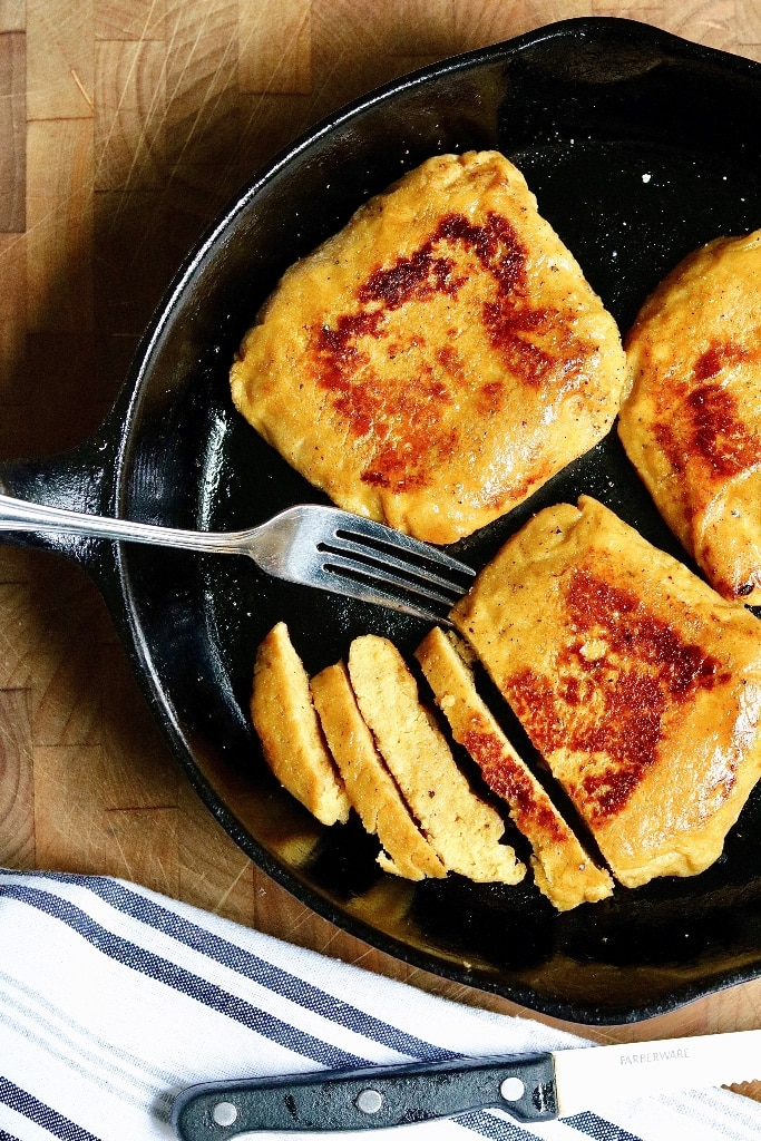 three vegan chicken breasts cooked in a frying pan partially sliced