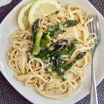 vegan lemon asparagus pasta on a white plate with lemon slices