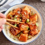 general tso's tofu in a bowl with rice