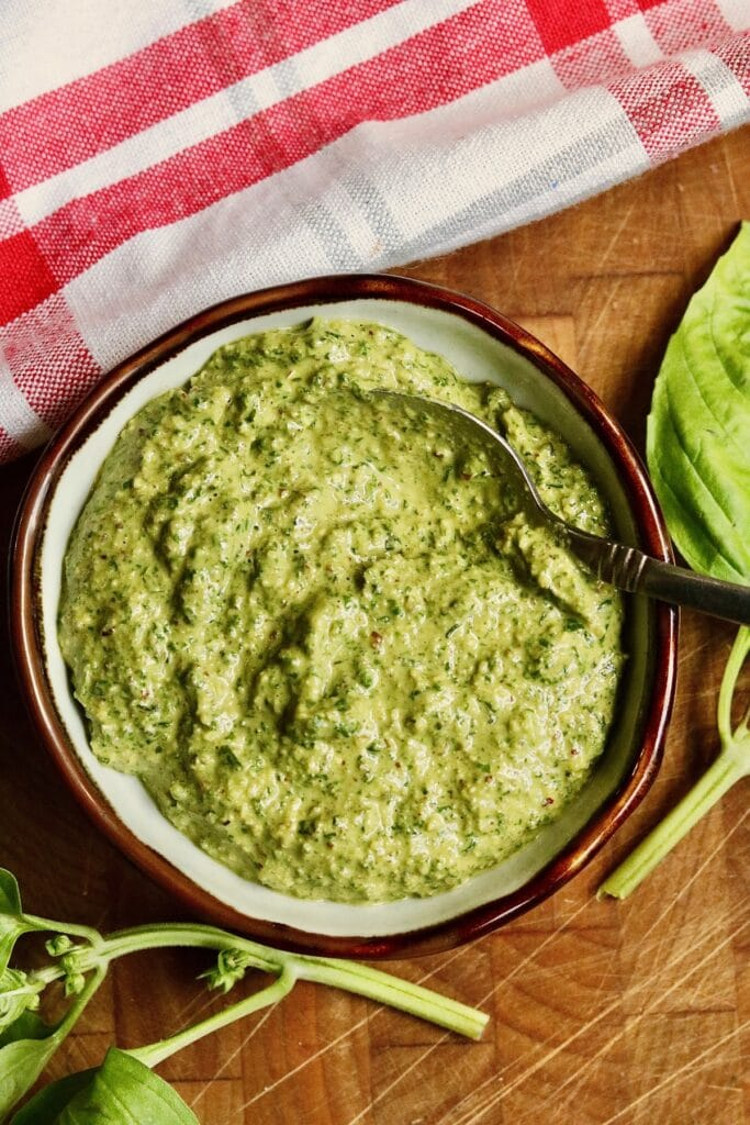 vegan pesto in a bowl with a spoon ready to serve