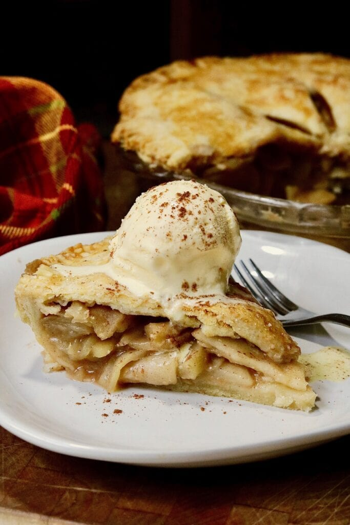 a slice of vegan apple pie with a scoop of dairy free ice cream on top