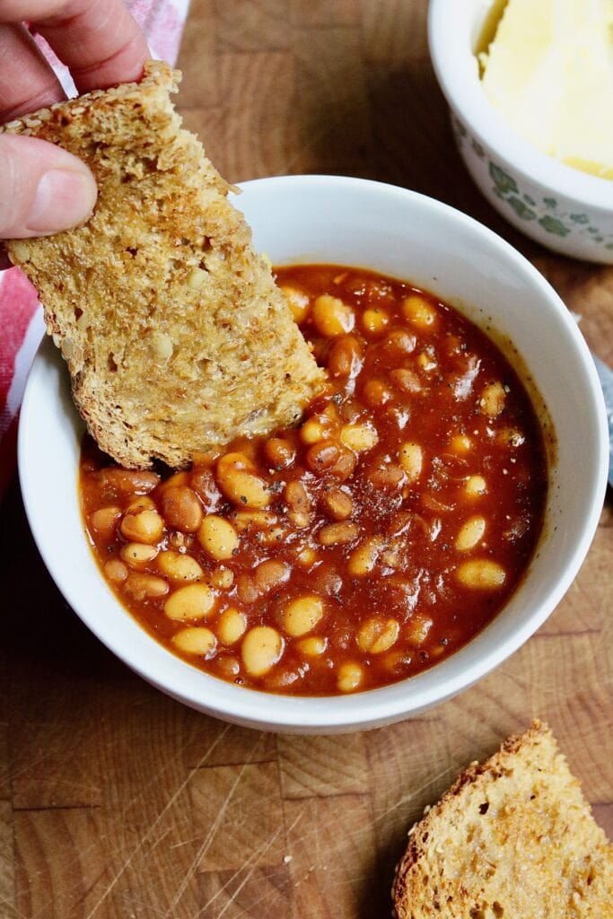 toast being dipped in a bowl of baked beans