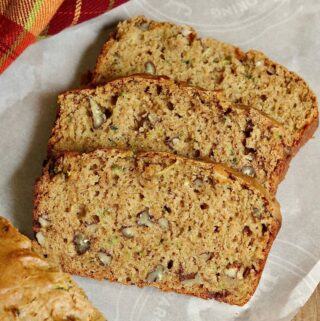 a loaf of vegan zucchini bread partially sliced on breakfast tray