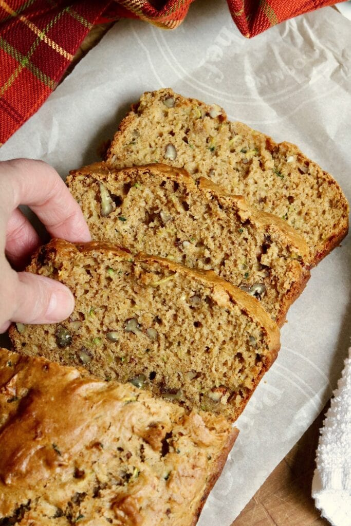 slice of vegan zucchini bread being picked up from a  breakfast tray