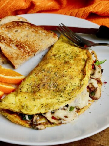 just egg omelette on a white plate with toast and orange slices ready to eat