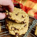 vegan pumpkin chocolate chip cookies stacked on a cooling rack
