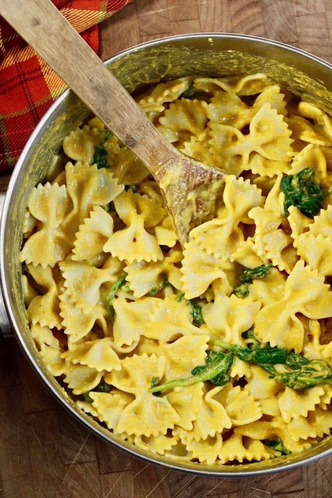 bowtie pasta in a pot tossed with vegan pumpkin pasta sauce